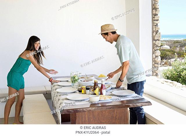 Couple arranging food on a dining table