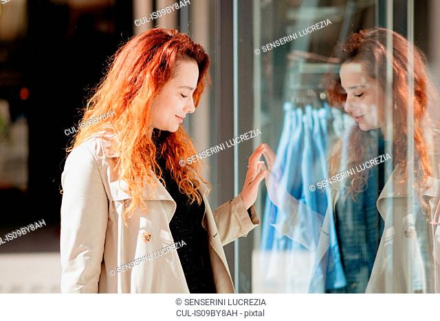 Woman looking into window of fashion boutique
