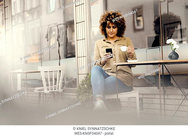 Woman in front of coffee shop, drinking coffee, holding smart phone