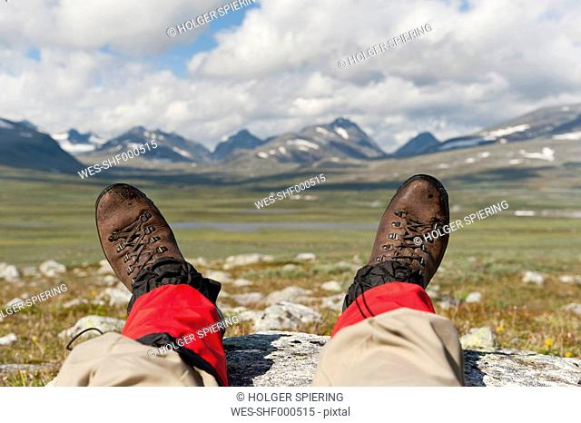 Sweden, Lapland, Hikers resting with parte ranges in background