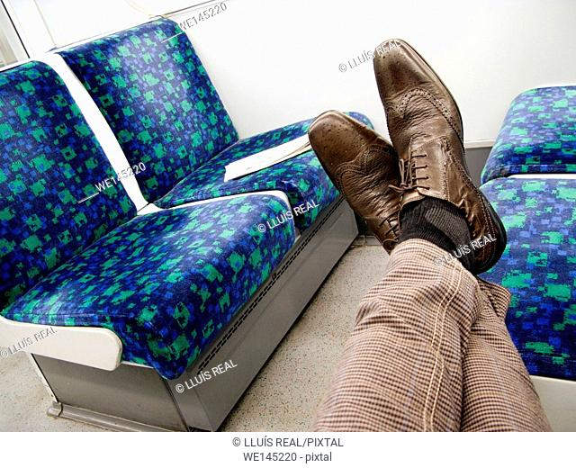 Legs of man with checkered pants and brown oxfords supported in a seat of a train wagon