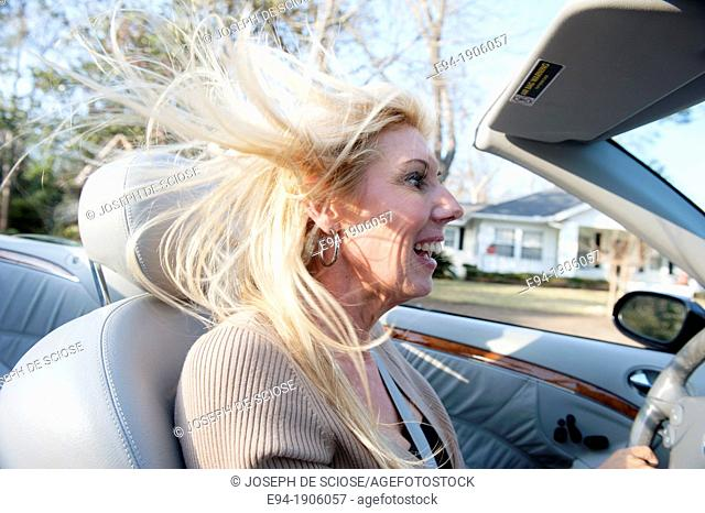 A 48 year old blond woman talking and being expressive while driving her convertible car