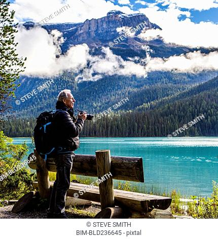 Caucasian man photographing mountain lake