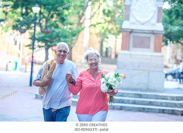 Portrait of happy senior couple carrying baguettes and bouquet in city