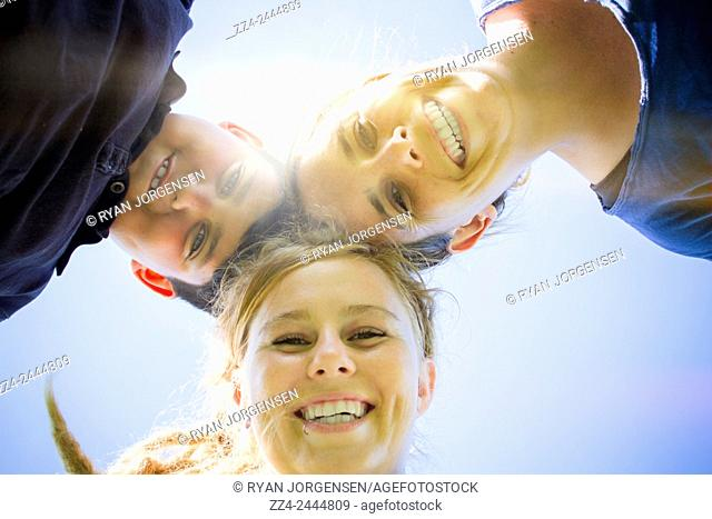 Outdoors portrait on the faces of a happy family smiling in a sun light summer garden
