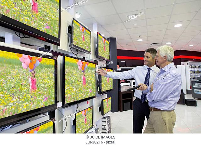 Salesman showing senior man flat screen televisions in electronics store
