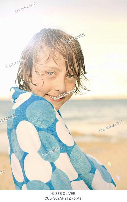 Boy on beach, wrapped in towel
