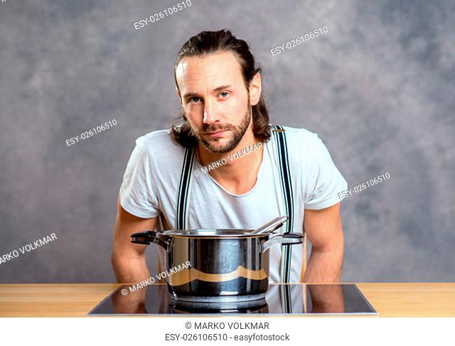 young bearded man with cooking pot in front of gray background