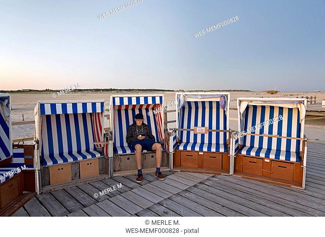 Germany, St Peter-Ording, teenage boy with smartphone sitting in hooded beach chair