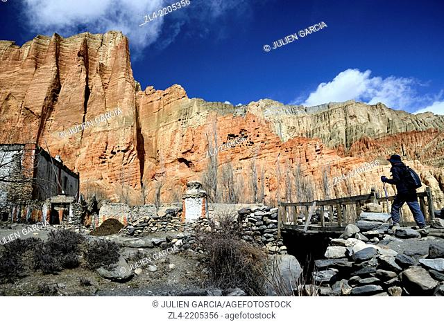 The village of Dhakmar and red cliff with caves. Nepal, Gandaki, Upper Mustang (near the border with Tibet). Model Released