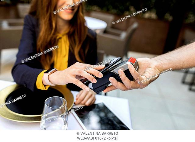 Woman paying with smartphone in a restaurant