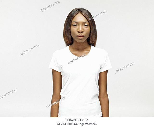 Portrait of serious looking young woman wearing white t-shirt
