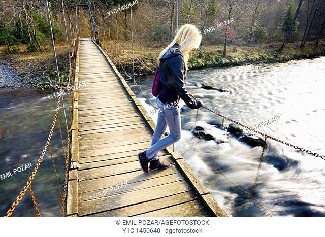 Attractive young woman on a hanging footbridge