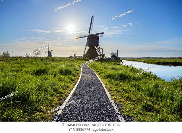 Gravel path with Windmills and sun, Kinderdijk, South Holland, Netherlands