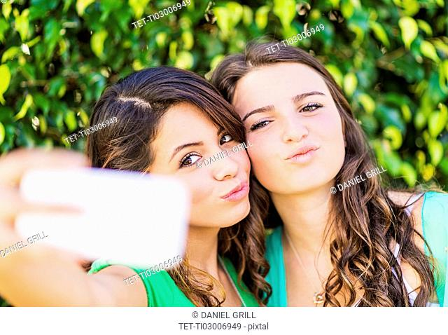 Portrait of female friends (14-15) making selfie