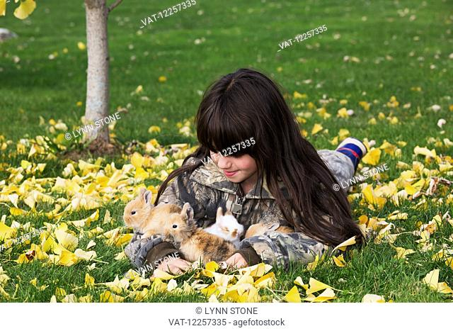 Young girl with mixed-breed rabbit babies; Higganum, Connecticut, United States of America