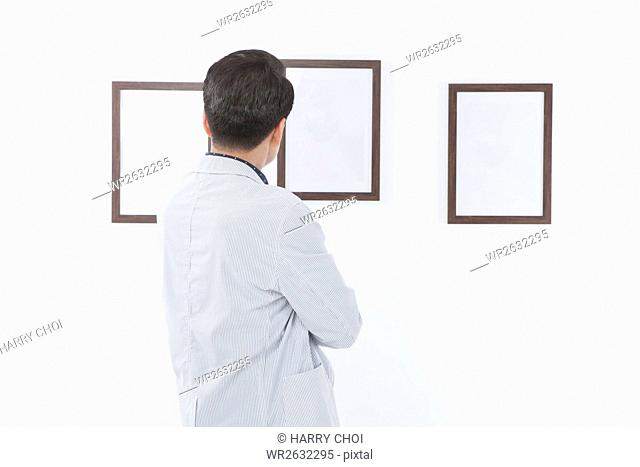 Back of middle aged man watching frames on wall folding his arms