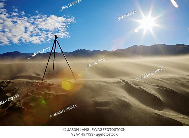 A tripod standing on the sand dunes at Great Sand Dunes National Park, Colorado on a windy day