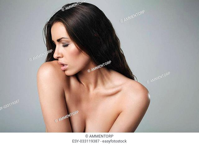 Seductive young woman topless on grey background. Sexy caucasian female model