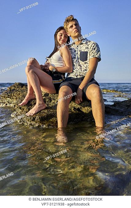 Couple sitting on rock in sea, vacations, love. Chersonissos, Crete, Greece