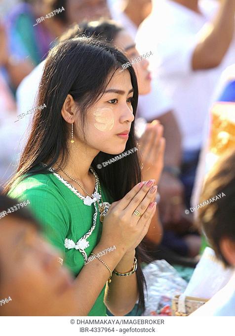 Praying woman at the Bigboon pilgrims' procession, meditation day of the Dhammakaya Foundation, Dawei, Tanintharyi Region, Myanmar