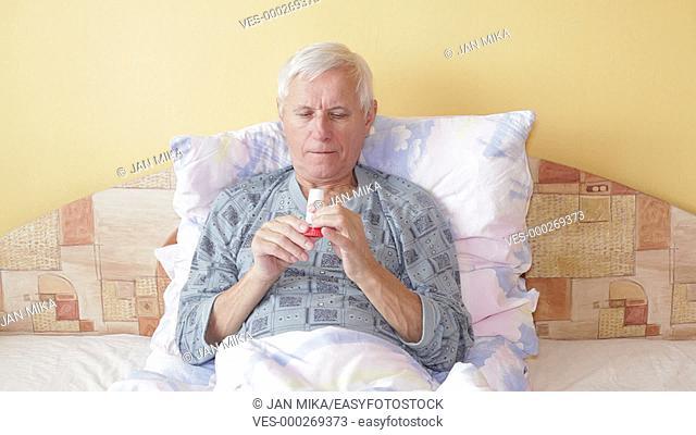 Senior man using asthma inhaler in bed