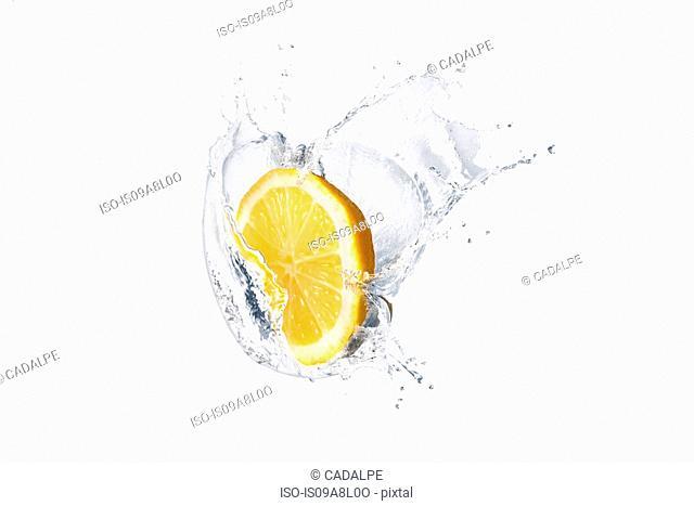 Slice of lemon splashing in liquid