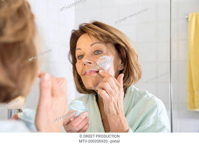 Reflection of a senior woman applying moisturizer on her face in mirror, Munich, Bavaria, Germany