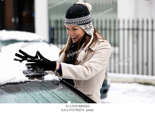 A young woman gathering snow off a car