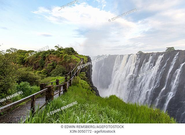 The rushing waters of Victoria Falls spray mist into the air which contribute to the areas thick, lush vegetation. Mosi-oa-Tunya National Park, Zimbabwe