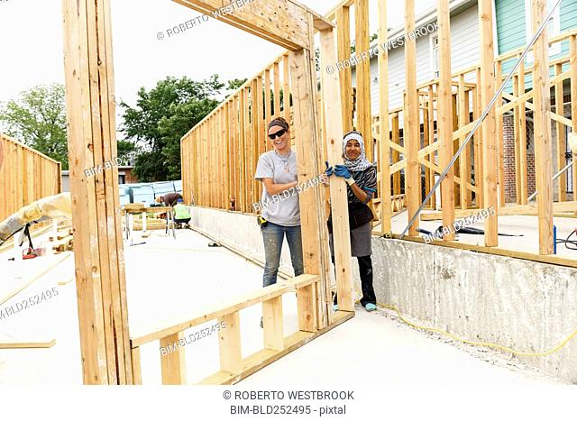 Smiling volunteers holding framed wall at construction site