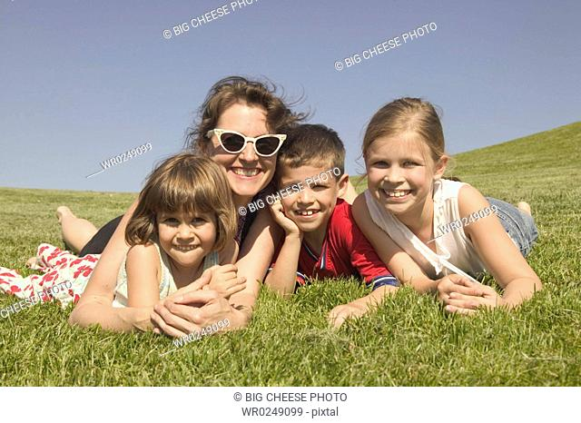 A mother laying in the sun with three children