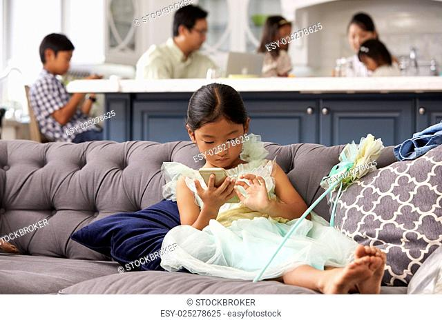 Young Girl Sitting On Sofa Using Mobile Phone At Home