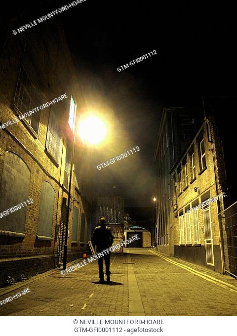 Silhouetted man walking down East End alley