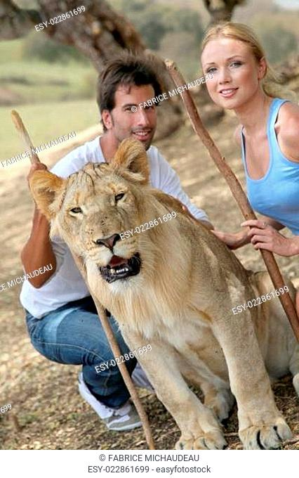 Couple sitting by lion in Savannah