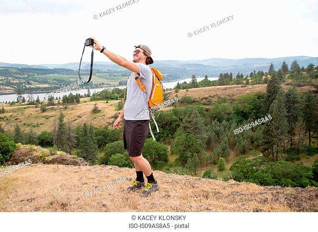 Young man, standing on top of mountain, taking self portrait with camera