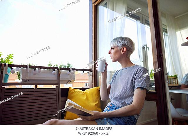 Woman reading book on balcony and drinking coffee