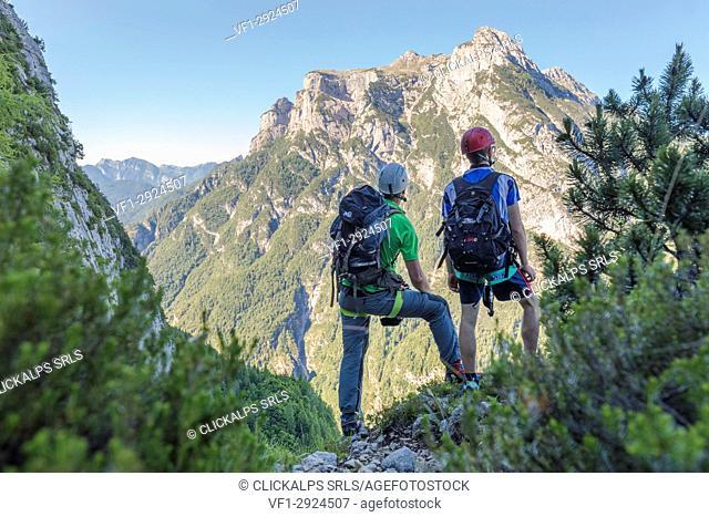 Europe, Italy, Veneto, Agordino, Dolomites, two mountaineers looking towards the Pale of San Lucano