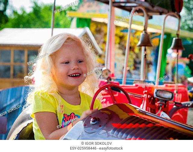 The child goes for a drive on a children's attraction