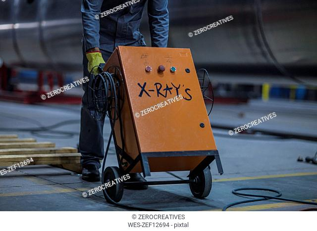 Close-up of worker walking with industrial machinery in factory