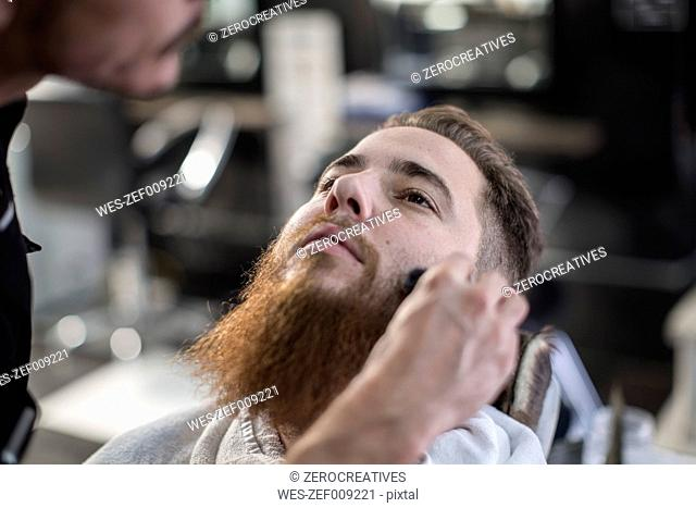 Barber brushes customers side hairs at barbershop