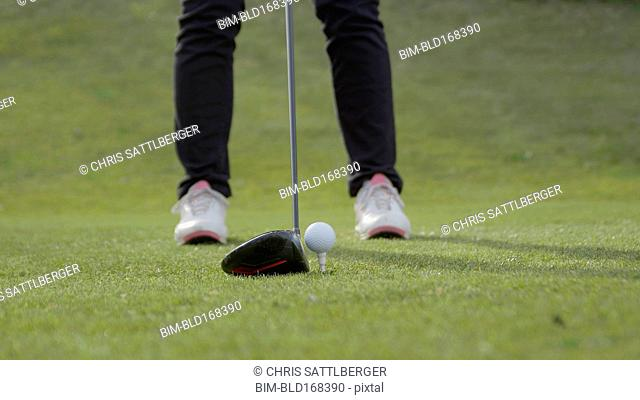 Caucasian woman teeing off on golf course