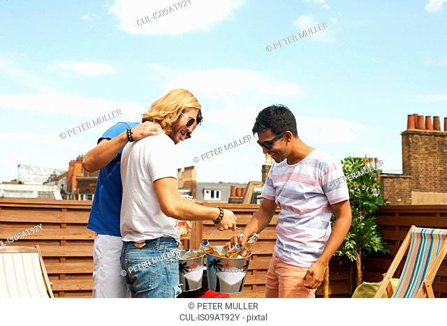 Three male friends with beer bottles and ice buckets at rooftop barbecue