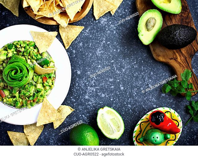 Traditional mexican sauce guacamole with fresh ingredients on stone background