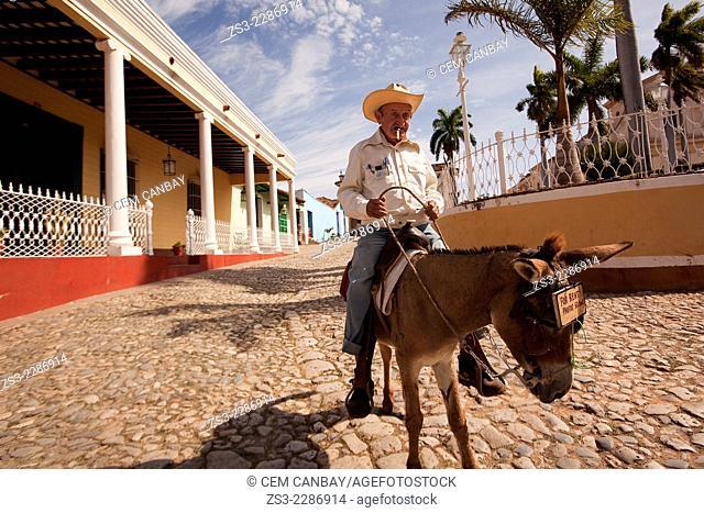 Old man riding on a donkey with the Iglesia de Santisima Trinidad Church at the background in town center, Plaza Mayor, Trinidad, Sancti Spiritu Province, Cuba