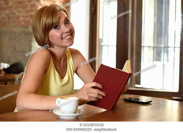 young pretty woman enjoying reading book at coffee shop drinking cup of coffee or tea smiling happy and relaxed in modern cafe