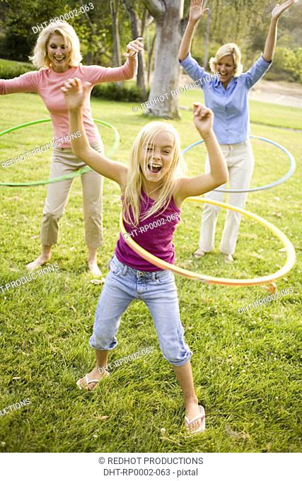 Grandmother, mother and daughter in park with hoola hoops