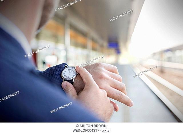 Businessman at station platform checking the time