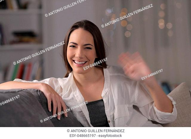 Happy woman greeting at camera in the night sitting on a couch in the night at home