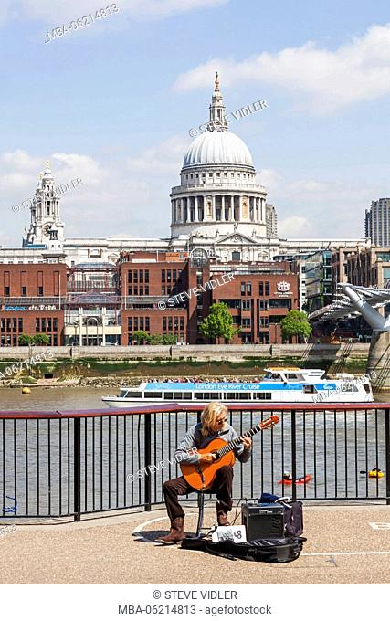 England, London, Bankside, Busker and St Pauls Cathedral